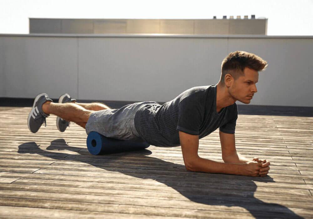 Homem usando o foam roller para massagear os quadríceps