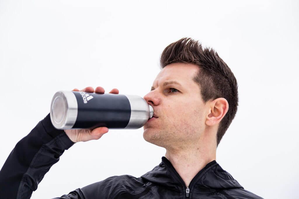 Un uomo reintegra i liquidi con uno sport drink durante l'allenamento