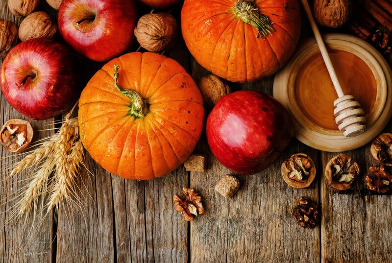 Photo de citrouilles, pommes, noix et miel sur une table.