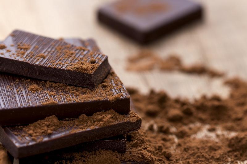 Dunkle Schokolade mit Kakao auf einem Holztisch