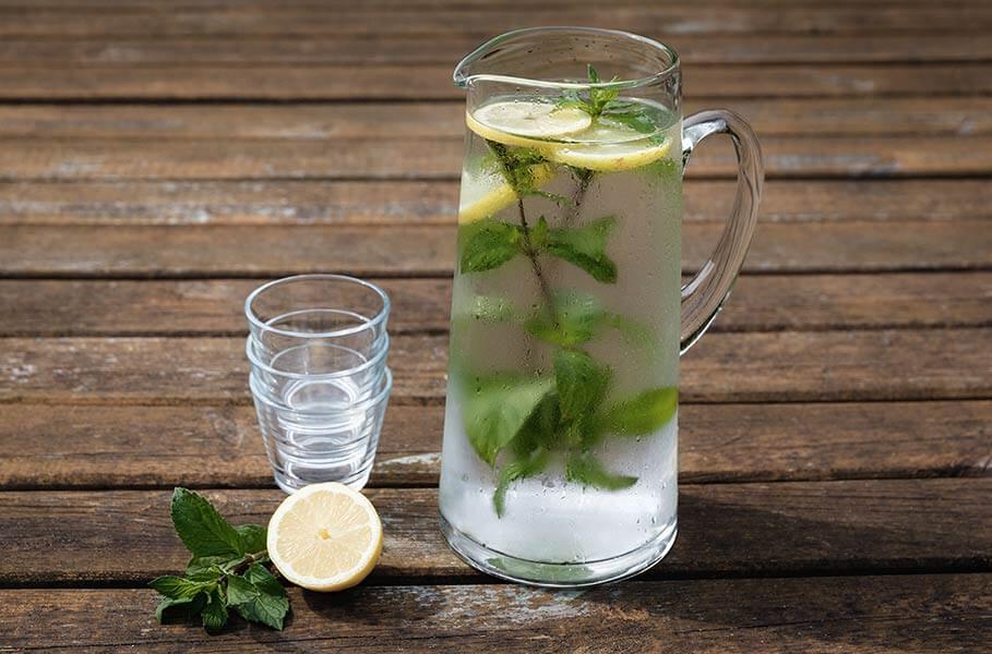 Eine Glaskaraffe mit Wasser, Minze und Zitronen