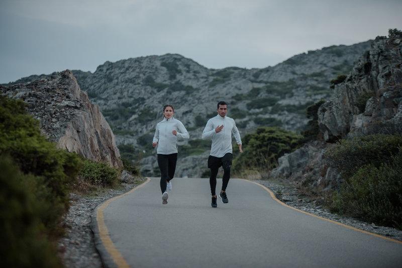 Una mujer y un hombro corriendo al aire libre