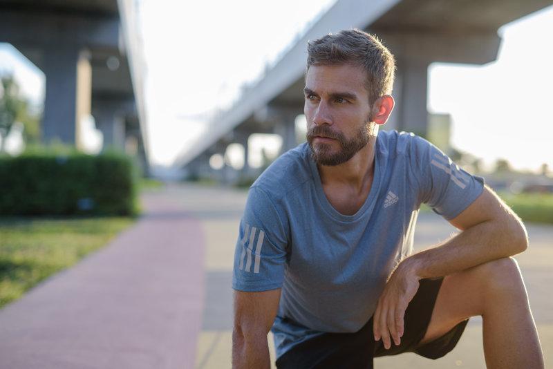 A man taking a short breaking during his run