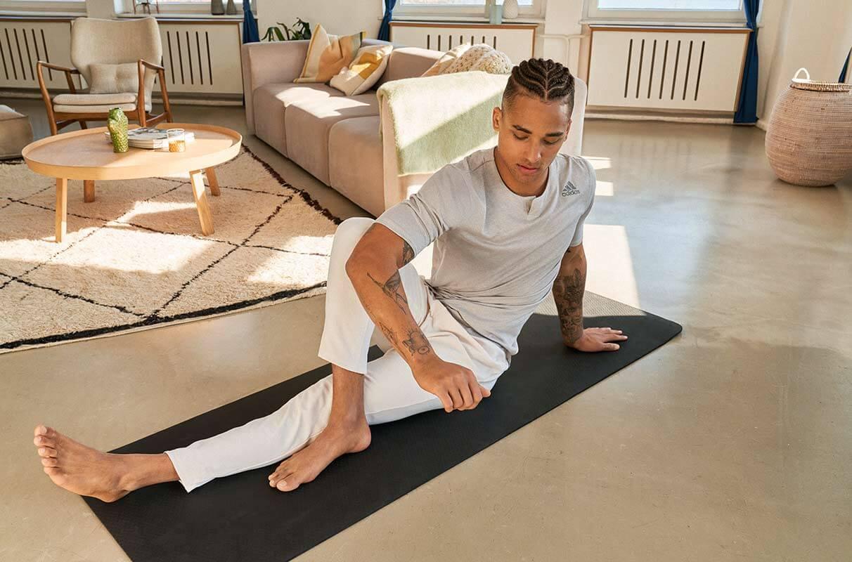 un uomo fa stretching sul tappetino a casa