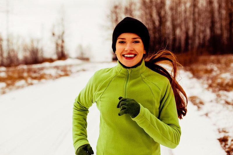 Glückliche junge Frau lauft im Winter