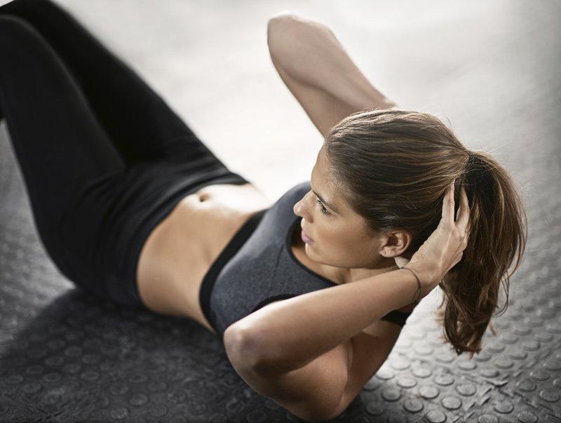 Huebsche junge Frau im Sportoutfit macht Sit-Ups