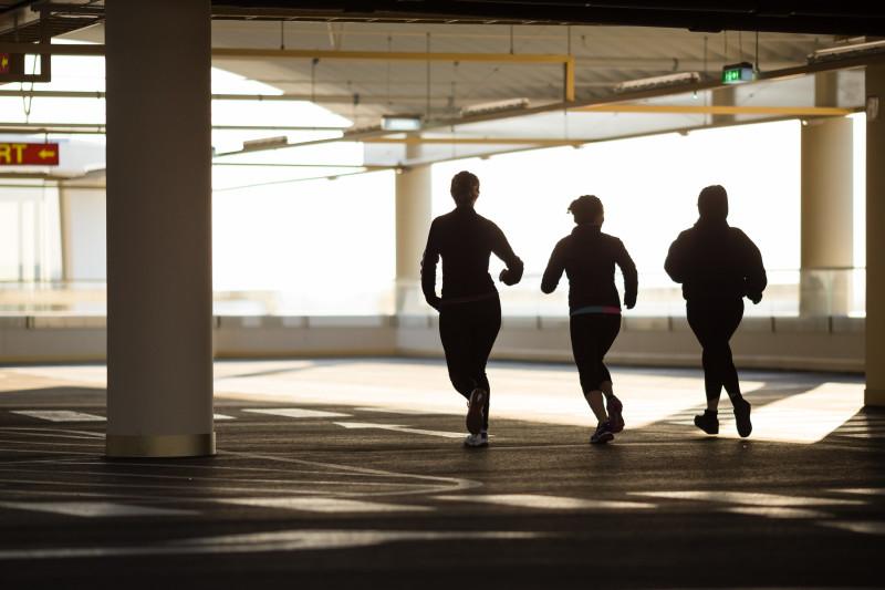 three women running in a underground carpark