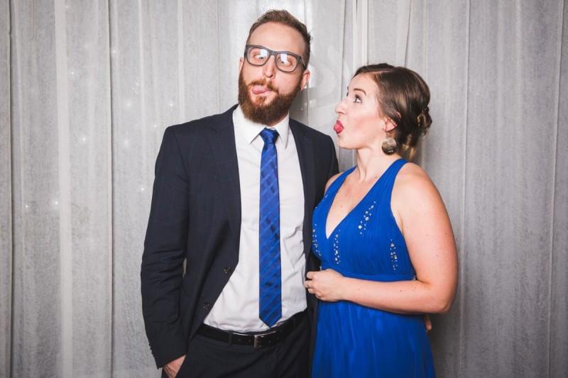 Junges Paar in Abendgarderobe zeigt ihre Zungen