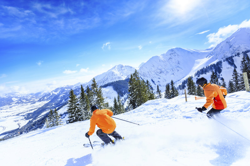 Two skiers skiing down in powder