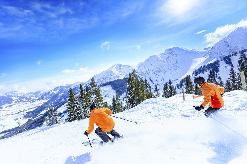 Zwei Skifahrer fahren nebeneinander auf der Piste