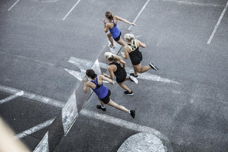 Foto von oben. 4 junge Frauen beim Laufen auf der Straße.