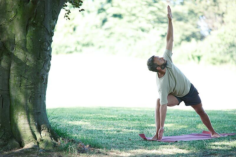 man doing a yoga pose in the park