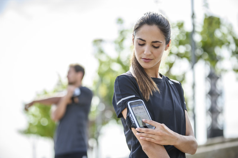 Women is checking her training session after running on her smartphone
