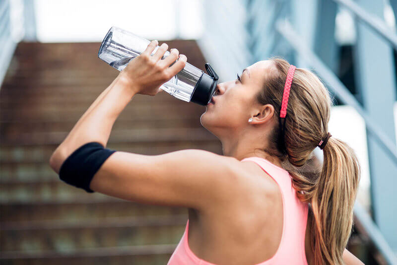 Young woman drinking from a water bottle after her run.