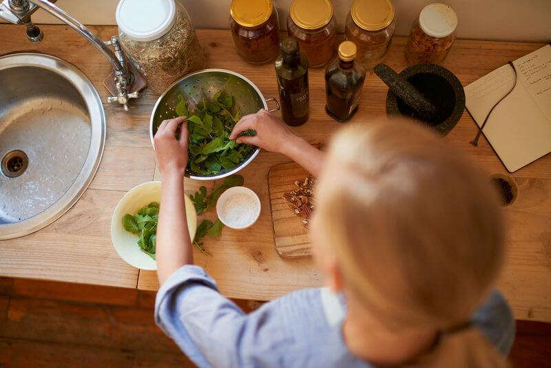 Frau beim Zubereiten von einem frischen gruenen Salat..