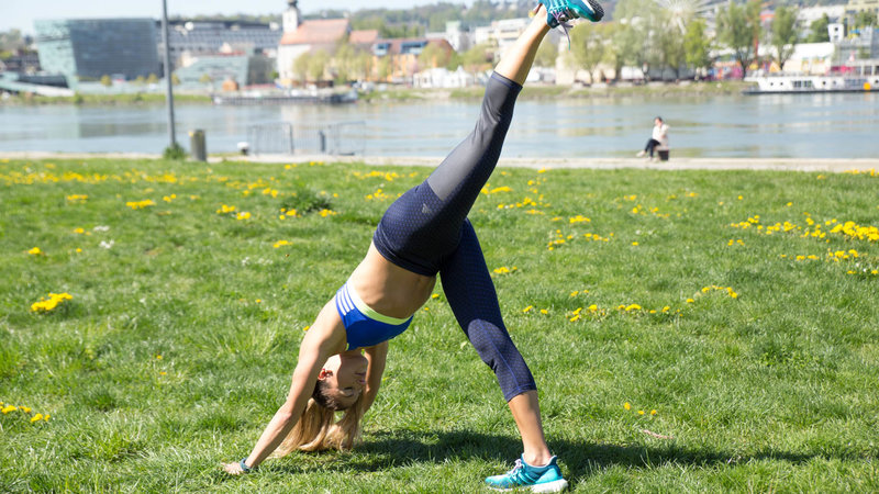 Young woman is doing a Single Leg Pike Push-Up.