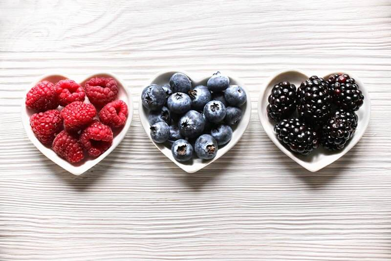 Raspberries, blueberries and blackberreis on heart shaped plates.