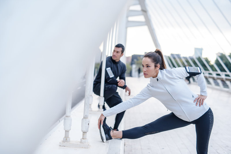 Eine Frau und ein Mann stretchen sich nach dem Lauf