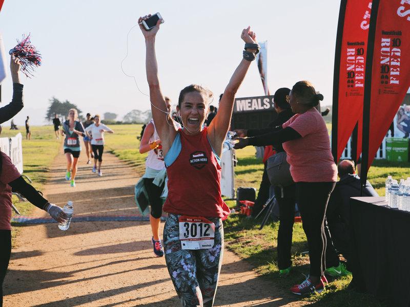 Eine erfolgreiche Läuferin erreicht die Ziellinie des Laufs RUN 10 FEED 10.