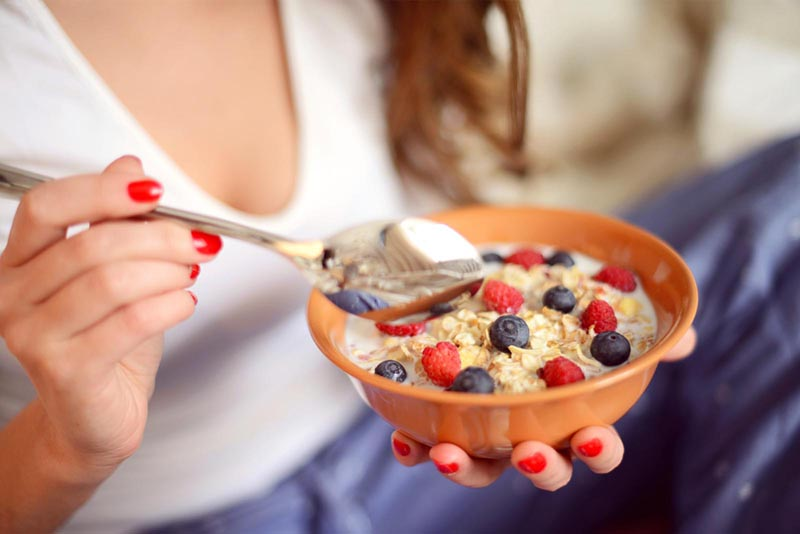 Close up of young woman eating a muesli with fruits.