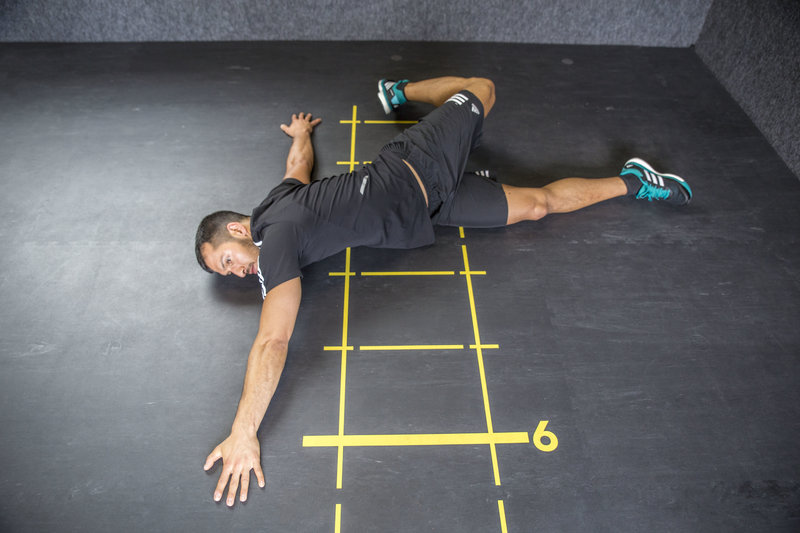 Young man who is doing the Scorpion 1 exercise.
