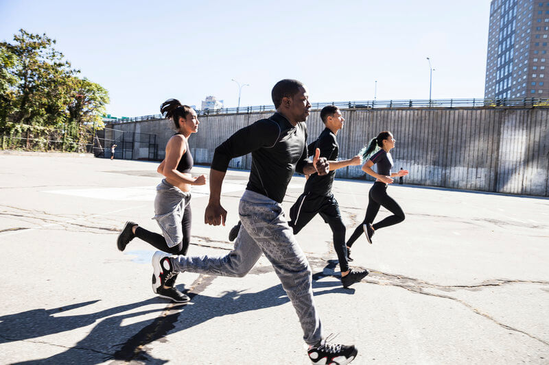 A group of two men and two women are doing a sprint.