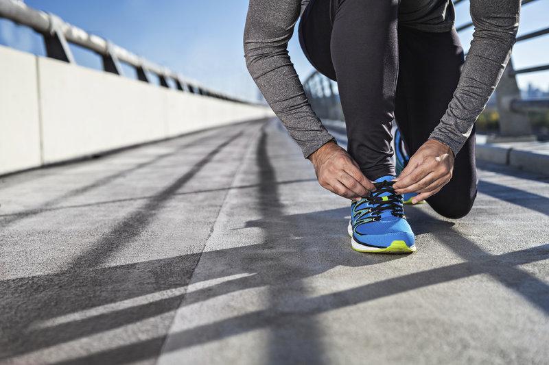 Mann schnürt seine Schnuhsenkel für seine Laufeinheit.