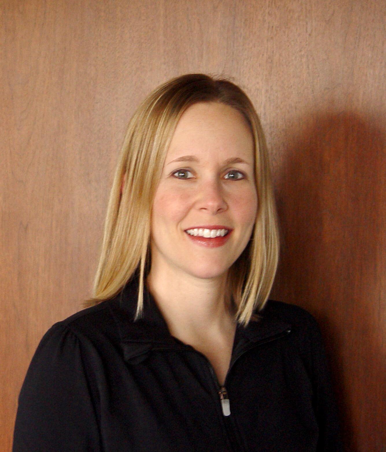 Eine blondhaarige Frau mit blau-grünen Augen.
