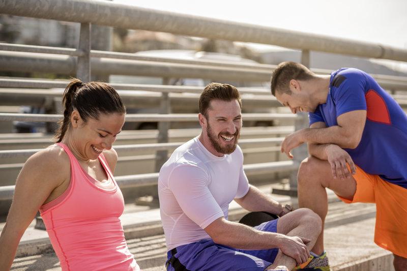 Eine Gruppe von jungen Menschen die nach dem gemeinsam Workout erschöpft und zufrieden beisammen sitzt.