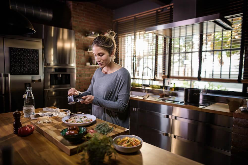 Donna in cucina che prepara da mangiare