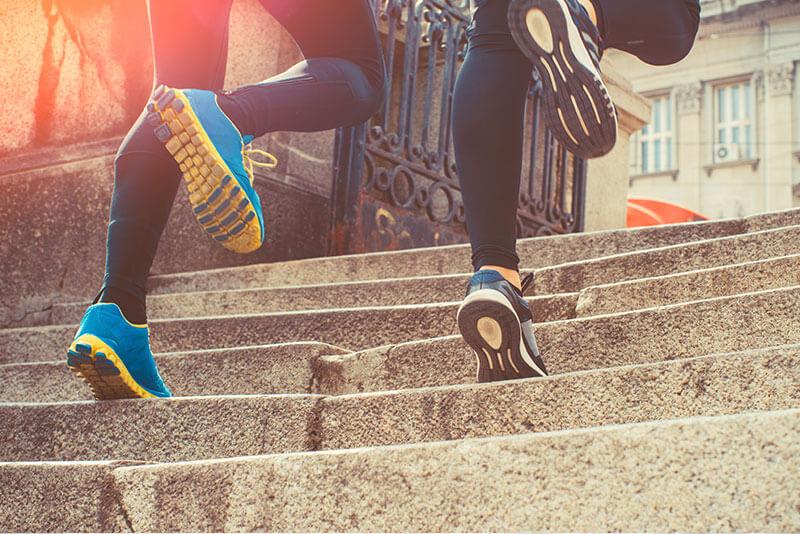 Bildausschnitt von zwei menschen die Stufen hinauf laufen.