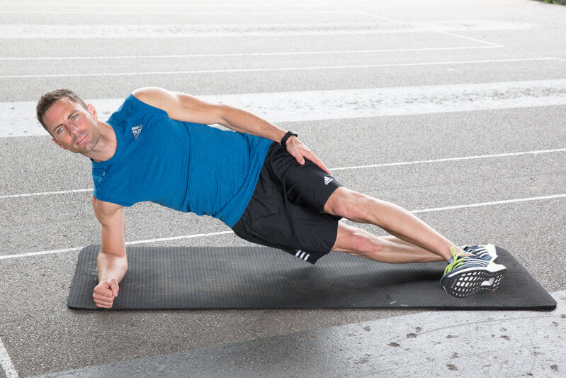 Homem fazendo prancha baixa lateral com movimento de perna.