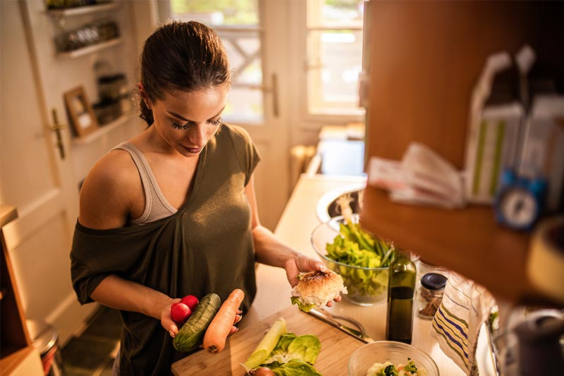 A woman who is preparing her meal with fresh vegetables.