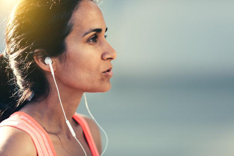 Junge Frau die läuft und Musik hört.