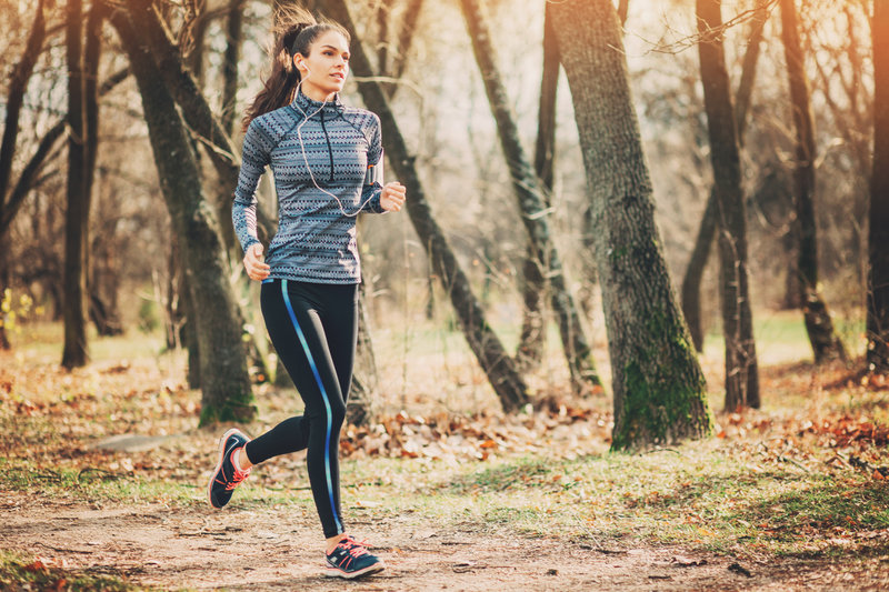 Eine junge Frau läuft im Herbst im Wald.