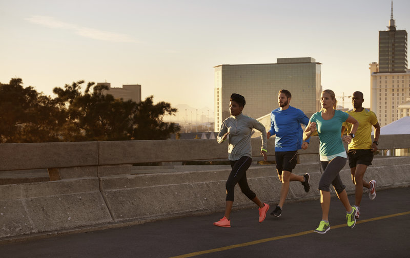 Shot of a group of young adults running with a city skyline in the background