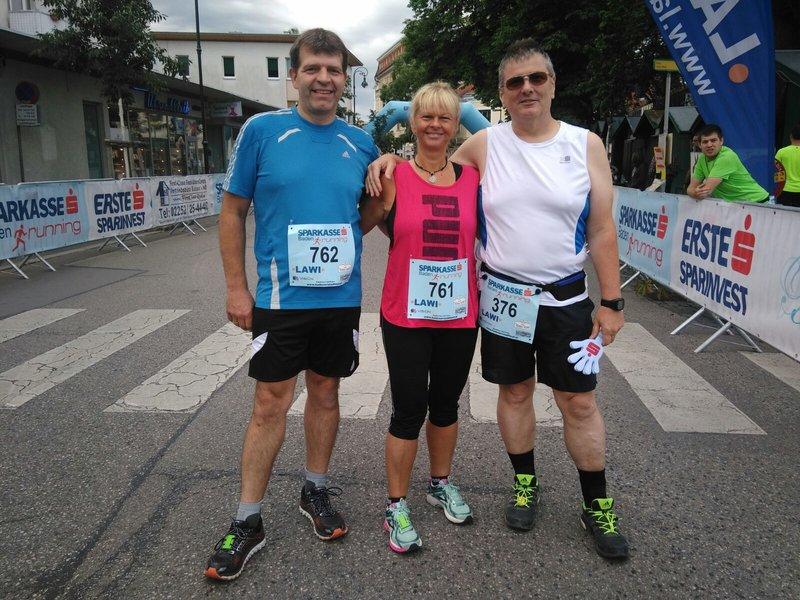 Drei Freunde bei einem gemeinsamen Foto nach einem Laufwettkampf.