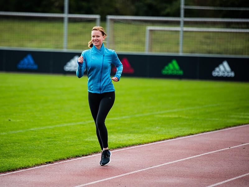 Junge Frau beim Laufen auf der Laufbahn.