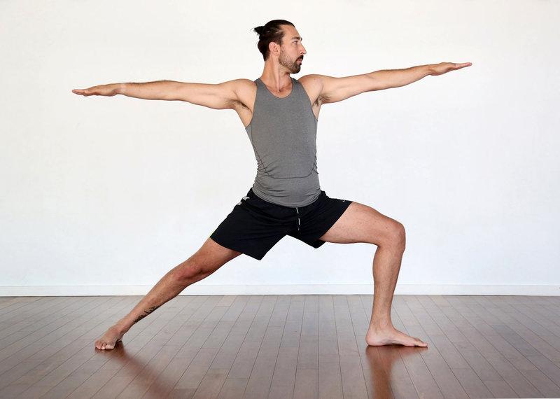 """Ein junger Mann macht die Yoga-Poste """"Warrior II""""."""
