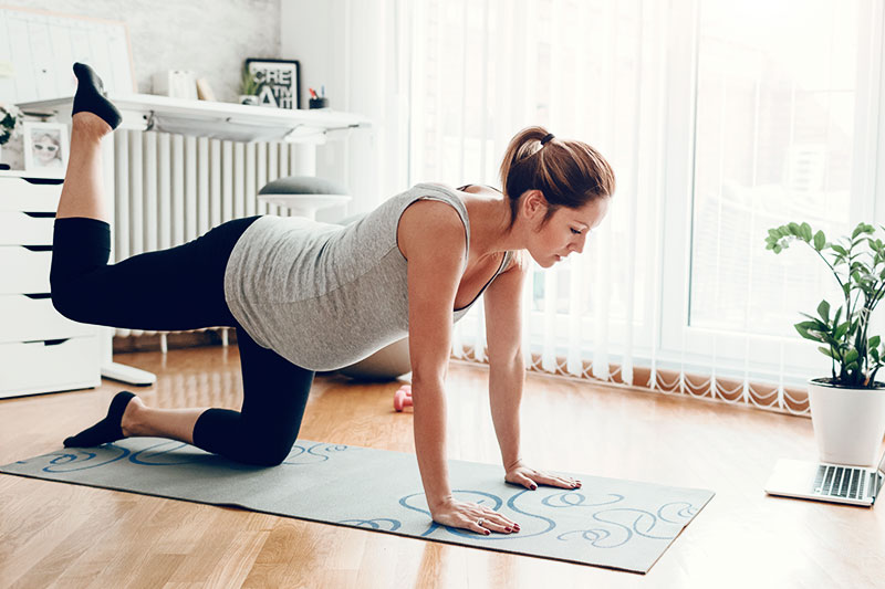 Pregnant woman doing a workout at home.