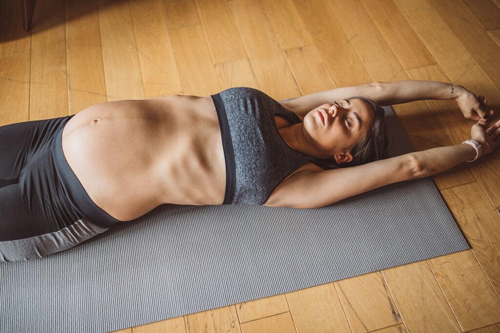 Una donna incinta fa yoga su un materassino