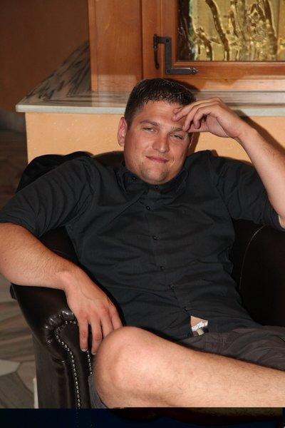 Junger uebergewichtiger Mann sitzt in seinem Wohnzimmersessel.