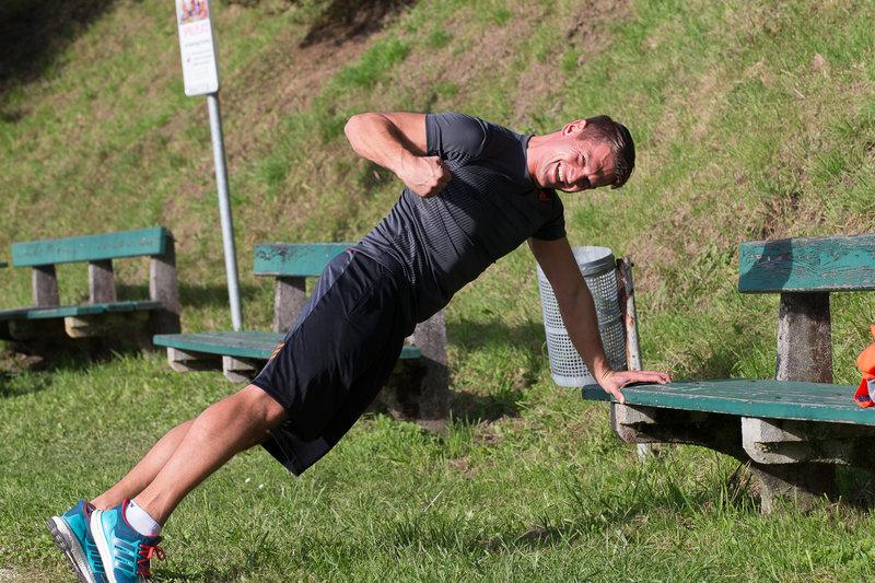 Junger Mann macht eine Plank im Freien.