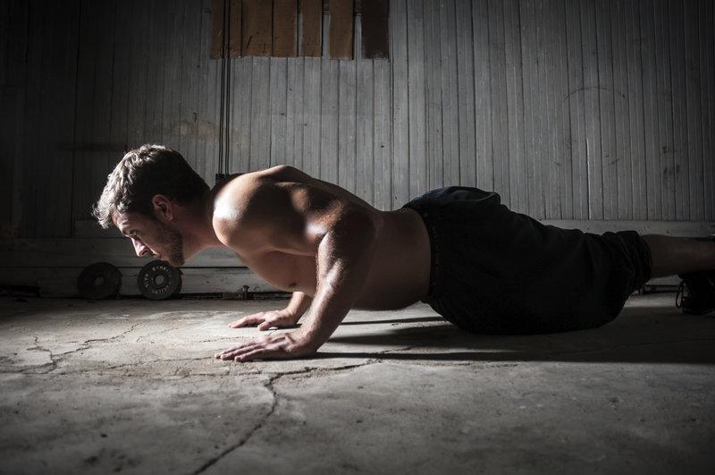 Athletischer Mann macht Liegestuetze.