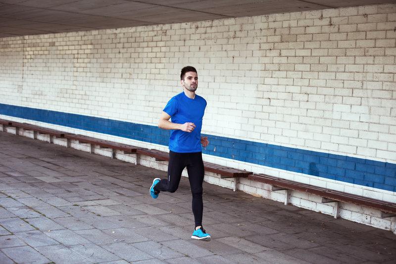 Junger Mann beim Laufen in der Stadt.
