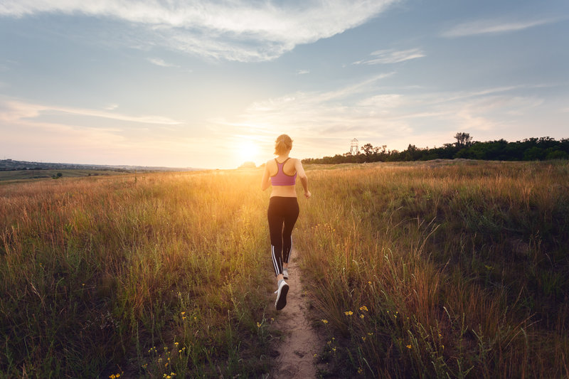 Young sporty girl running on a rural road at sunset in summer field. Lifestyle sports background