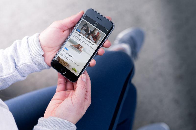 Junge Frau haelt ihr Smartphone mit der Runtastic Results App in den Haenden.