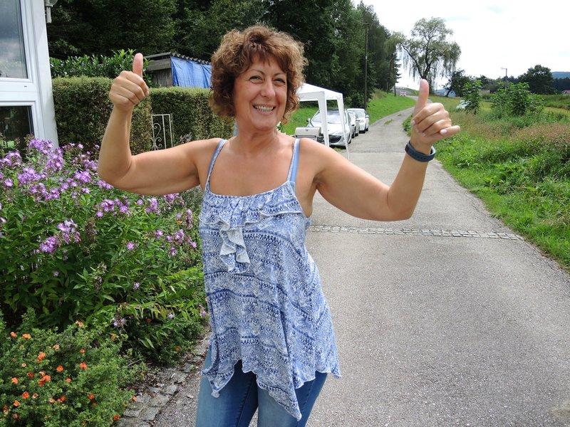 Froehliche Frau steht auf der Straße und lacht in die Kamera.