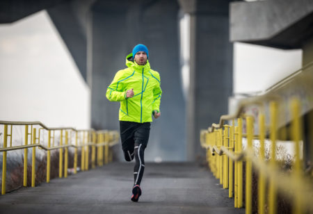 Sportsman running over the bridge during his cardio routine on a winter day. He is wearing green jacket and blue cap.