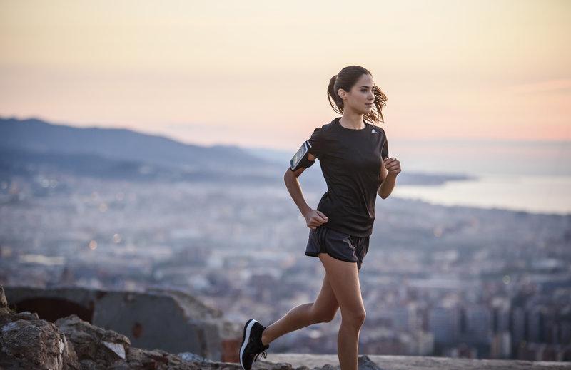Frau beim Laufen auf einer Bergstraße mit Blick ueber die Stadt.